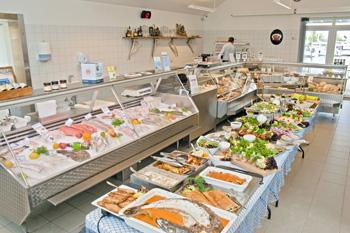 Fiskehusets butik med stort udvalg i fersk fisk, røget fisk, hjemmelavede delikatesser og THY-Sild m.v. Billedet er et aftenbillede med fiske- og skaldyrsbuffet stillet an i butikken.